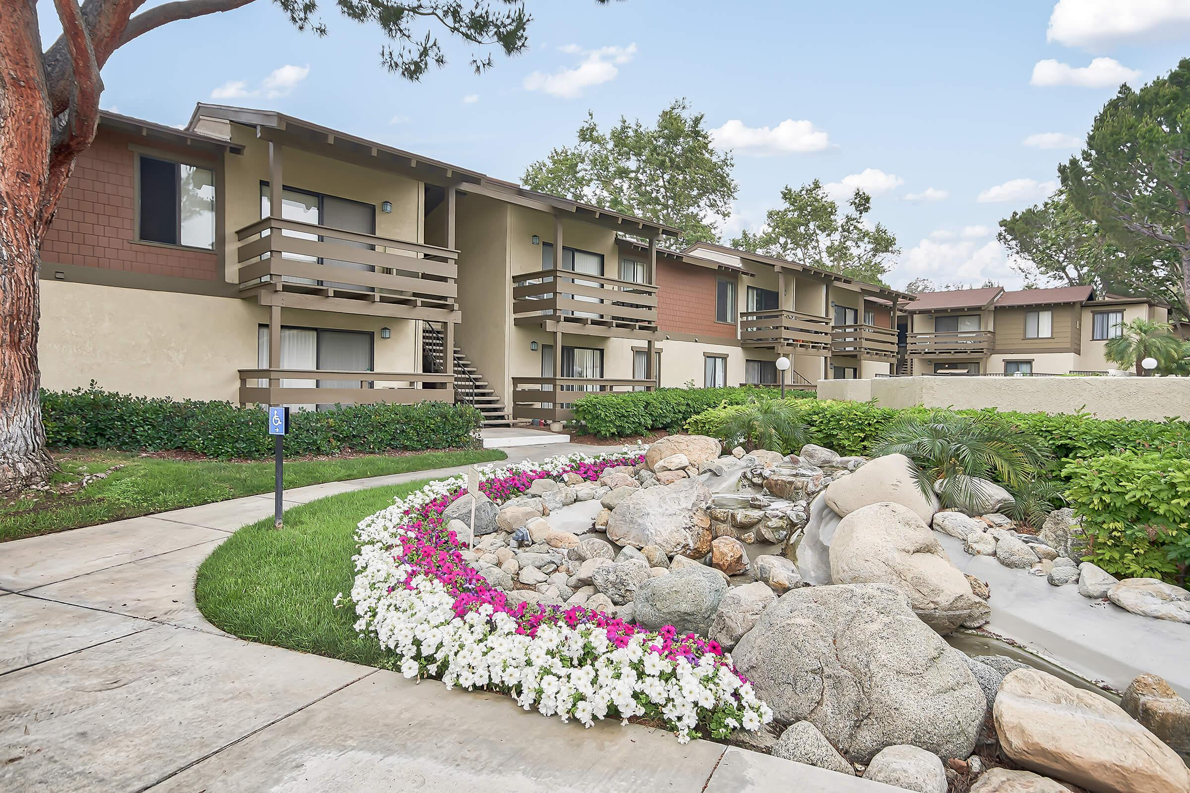 Raintree Apartment Homes community building with white and pink flowers