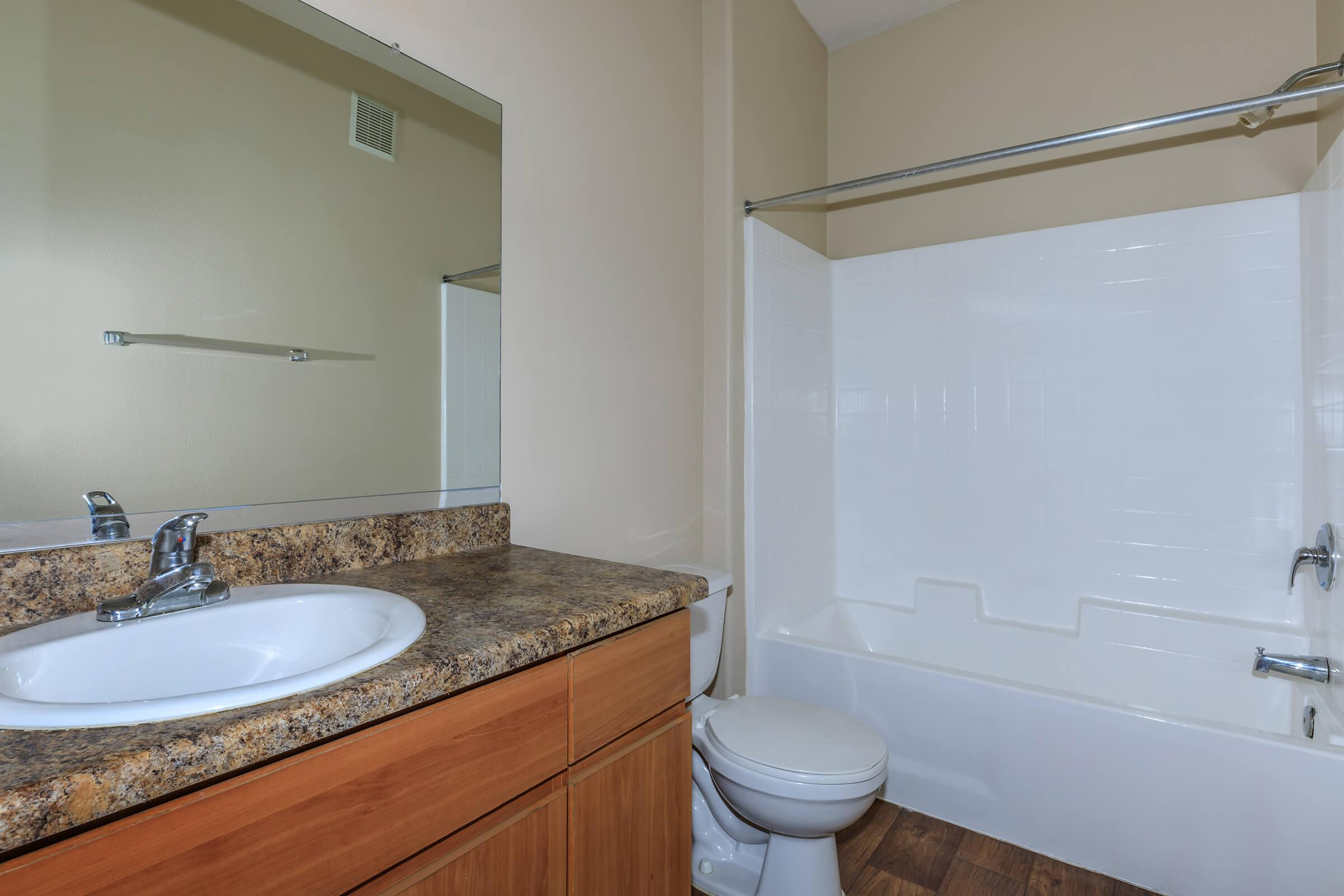 a large white tub next to a sink and a mirror
