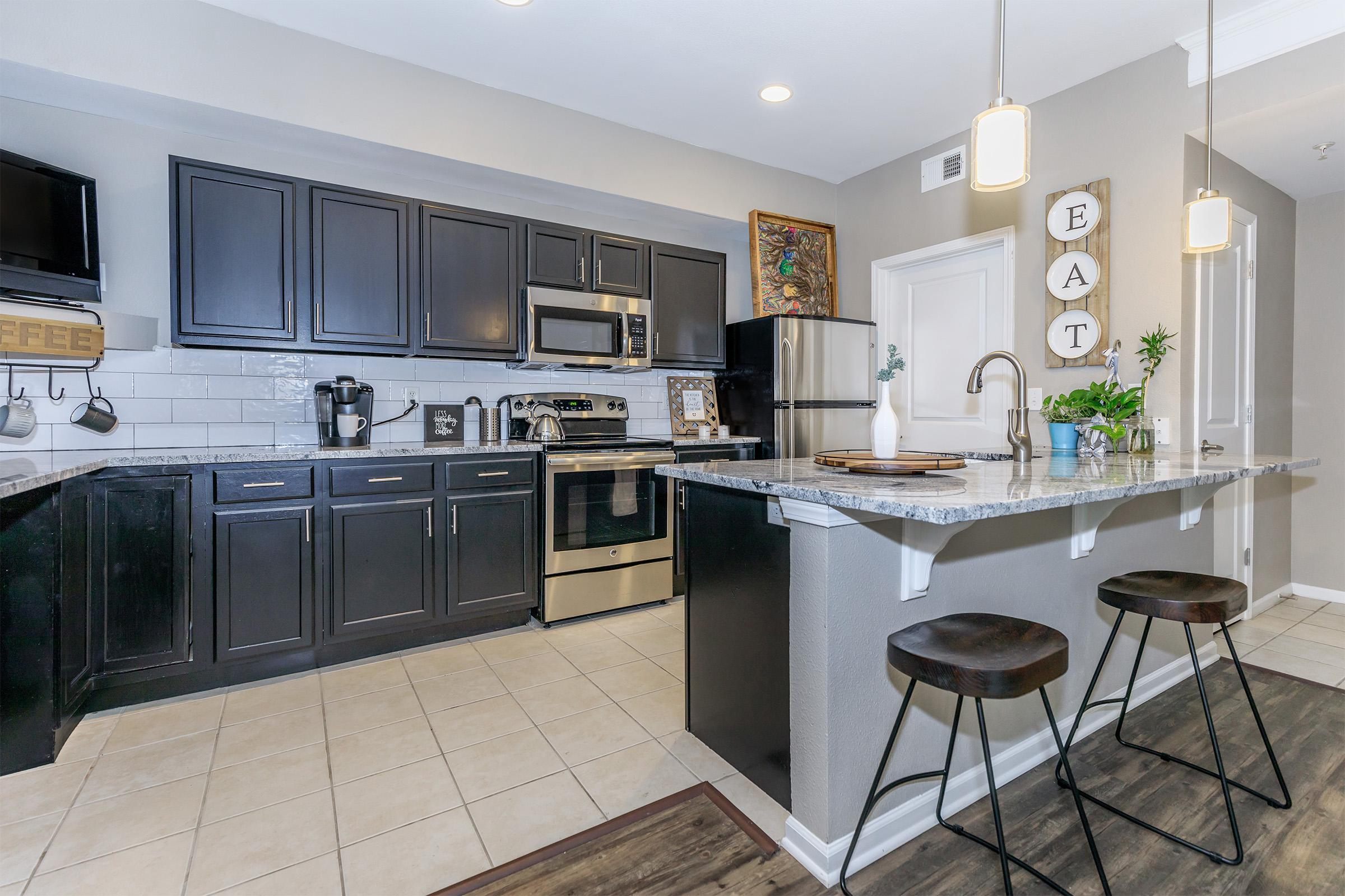 a kitchen with a sink and a chair in a room
