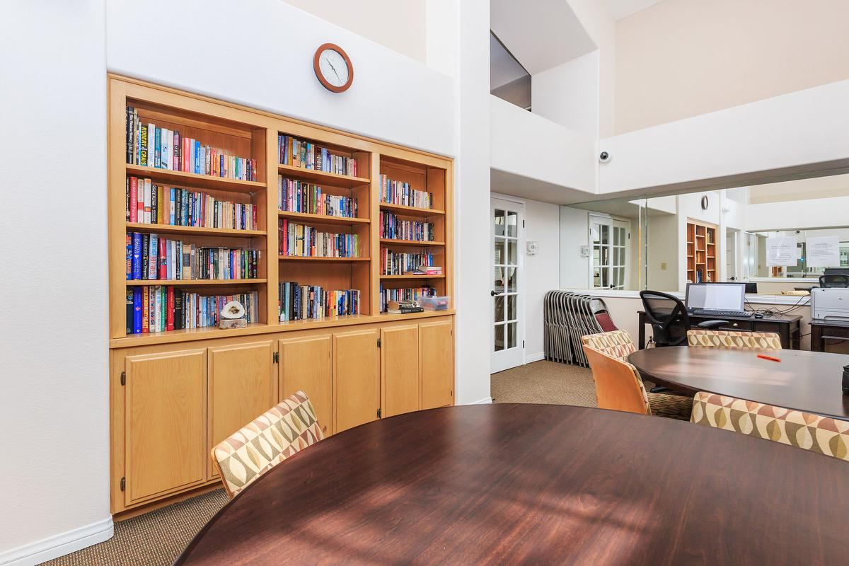 a living room filled with furniture and a table in a library