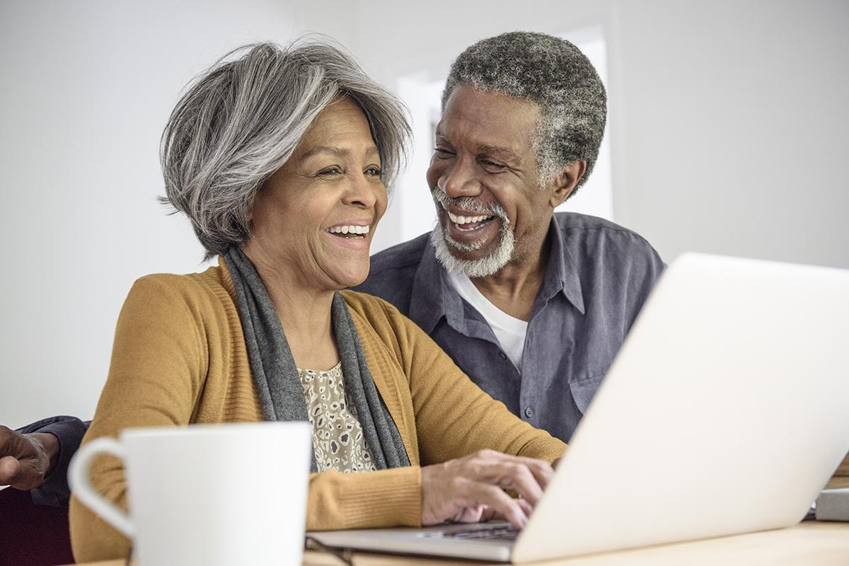 a man and a woman sitting at a table using a laptop