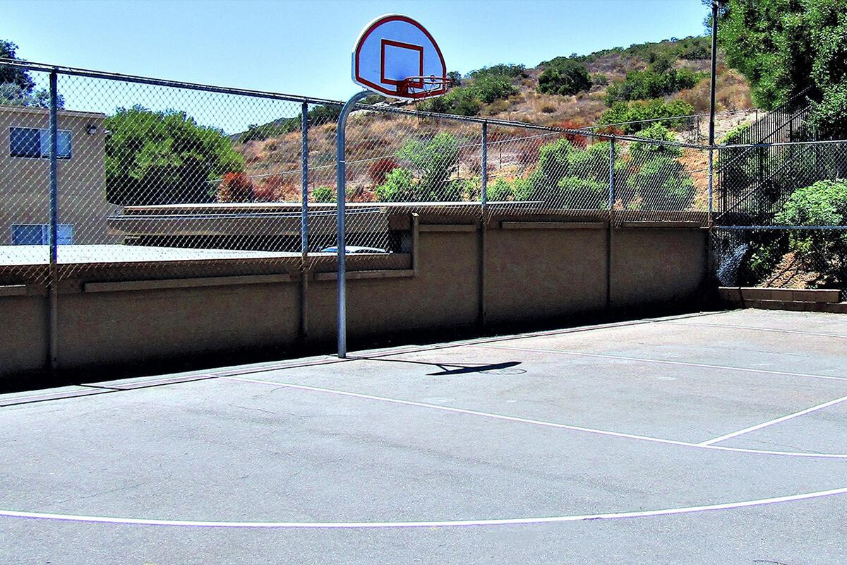 a basketball on a court with a racket with Barcelona Pavilion in the background