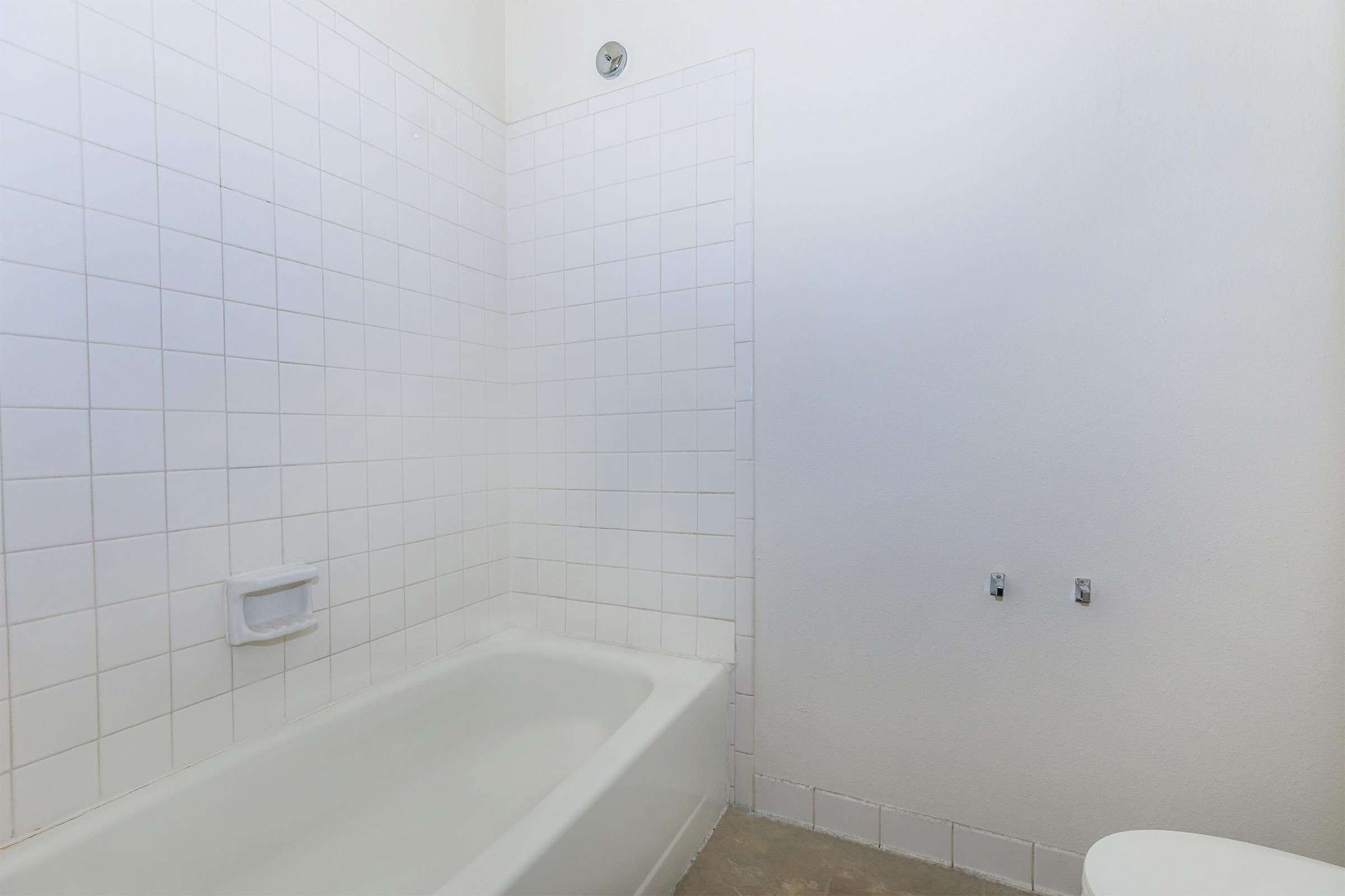 a large white tub next to a tiled wall
