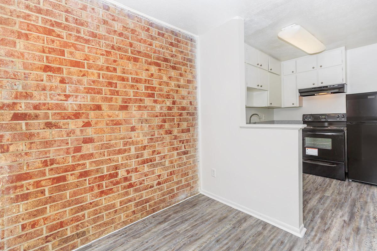 a kitchen with a stove and a brick wall