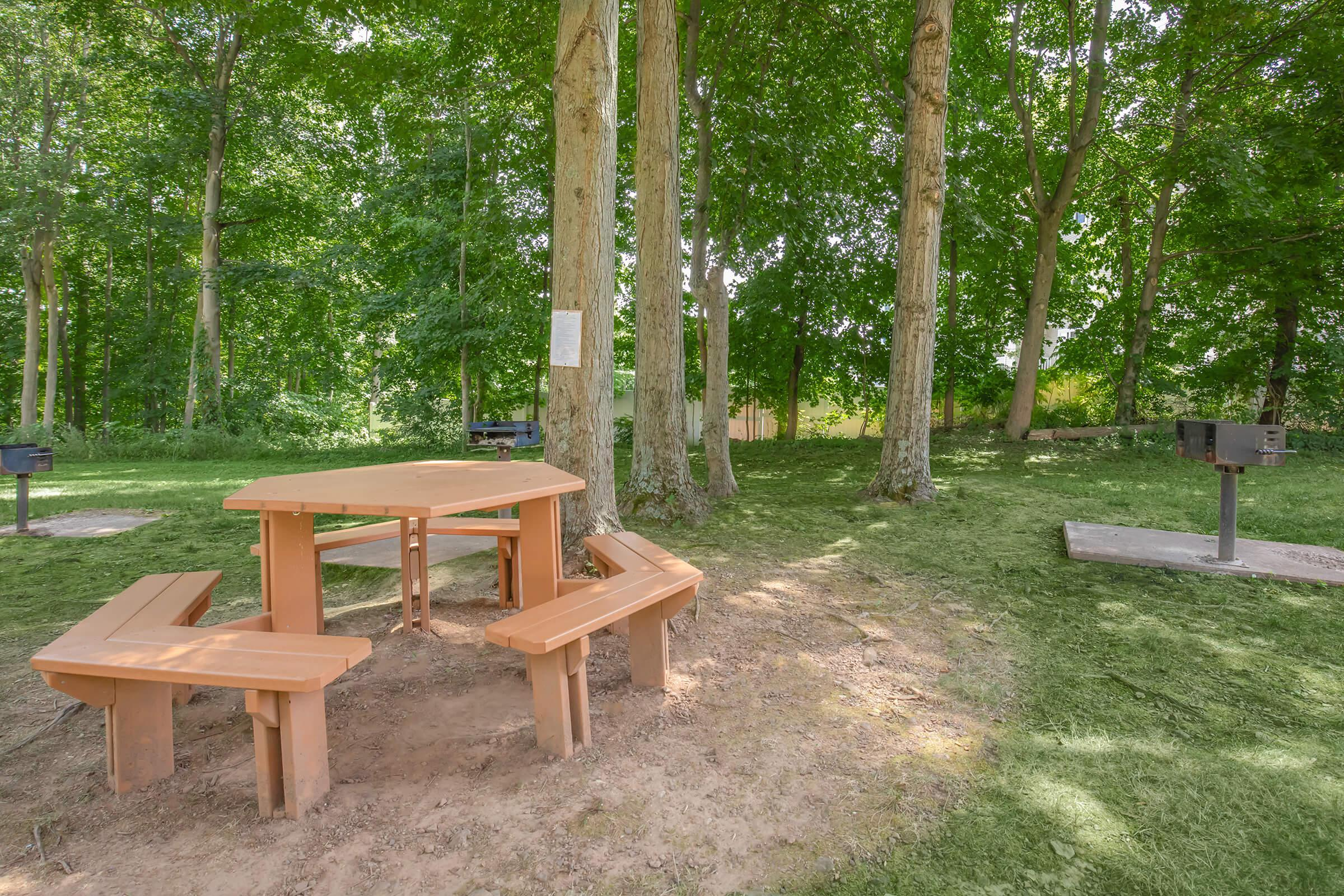 an empty park bench sitting on top of a wooden table