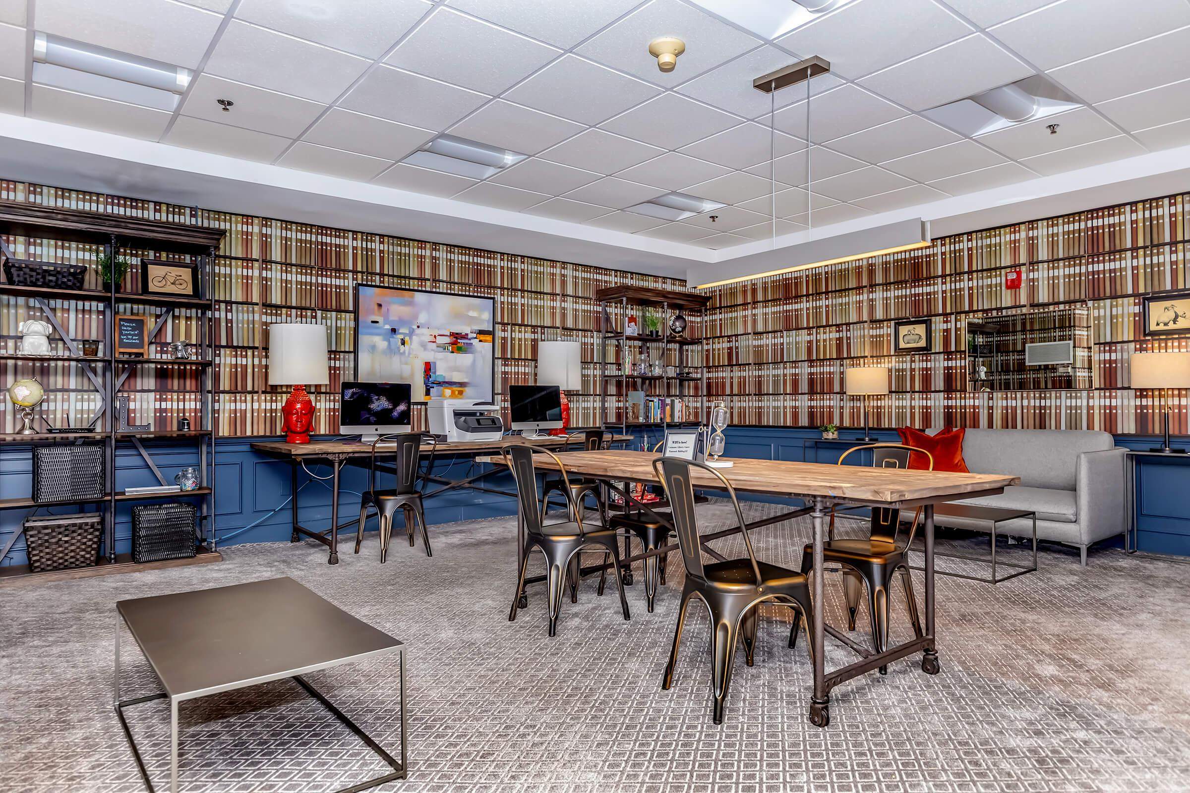a room filled with furniture and a table in a library