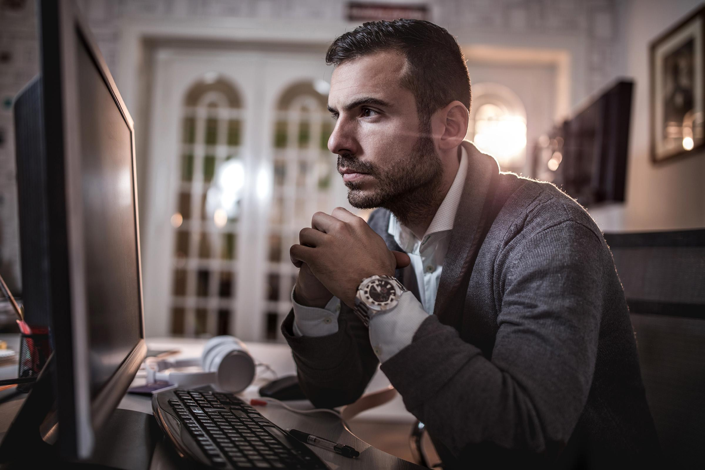 a man standing in front of a laptop