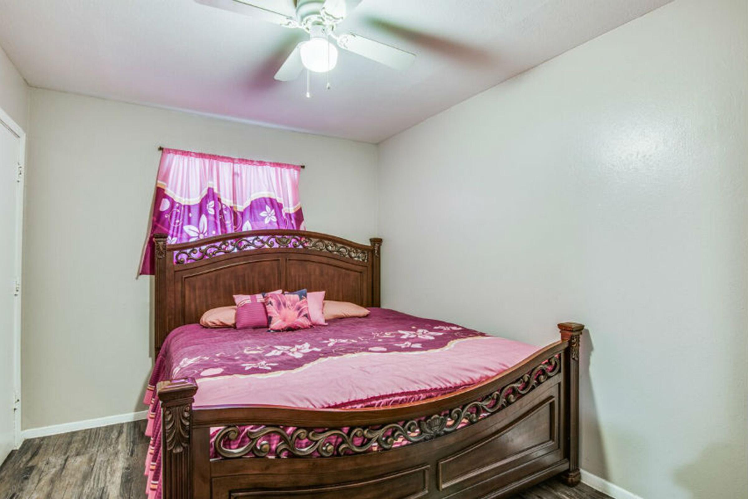 a bedroom with a pink blanket