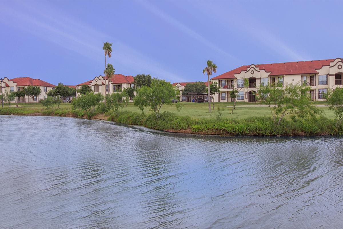 a house with bushes in front of a body of water