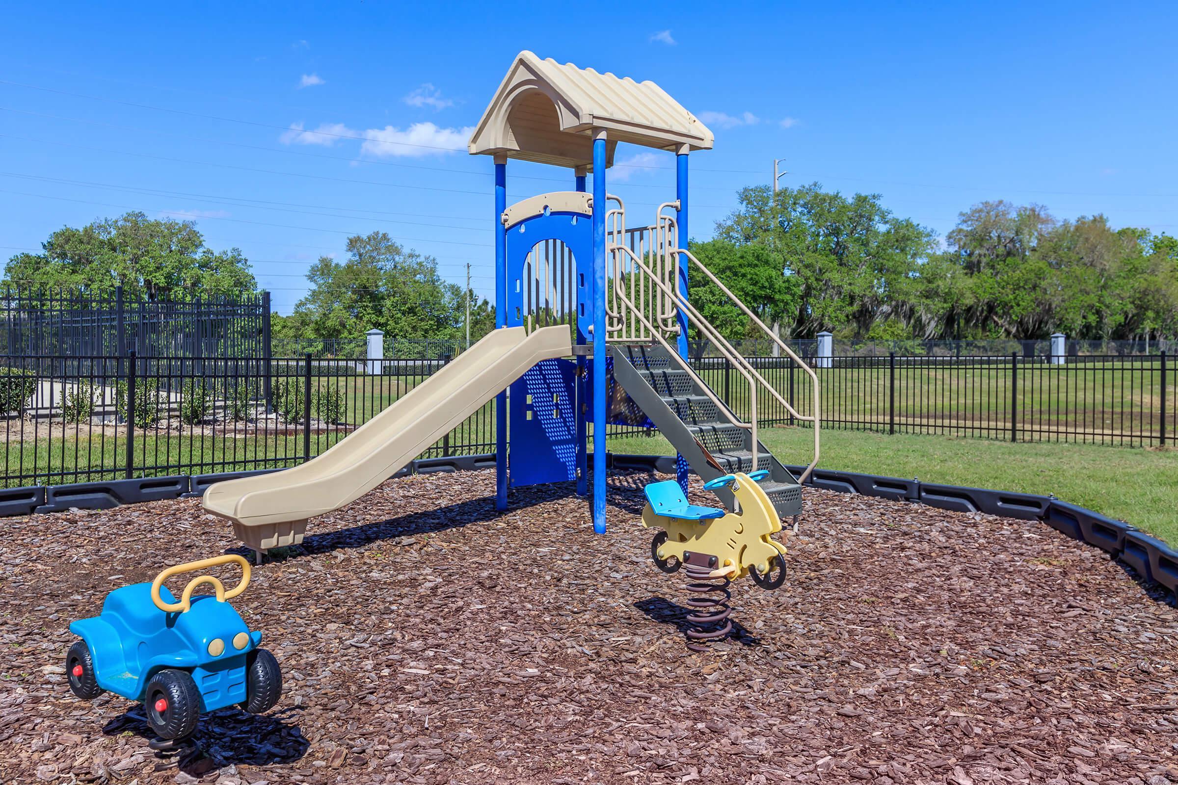 a playground with a blue umbrella
