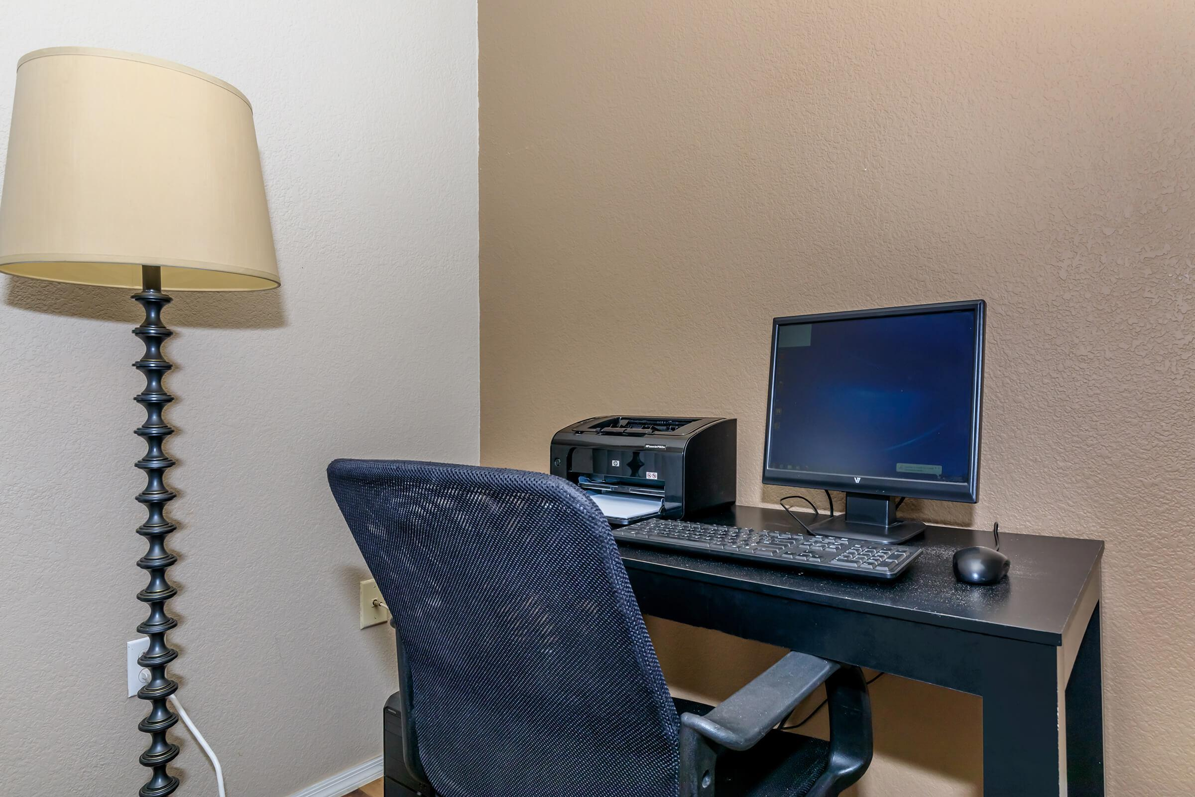 a desk with a laptop computer sitting on top of a chair