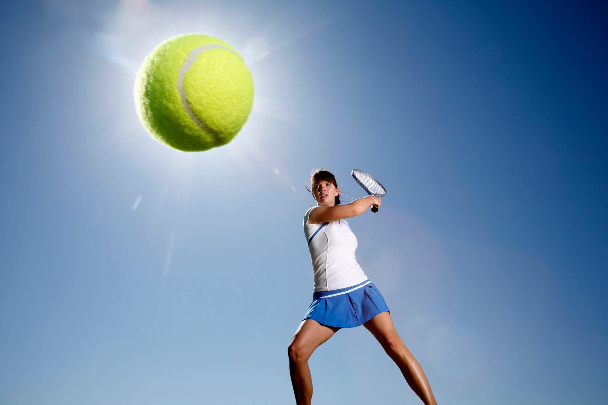 a woman hitting a ball with a racket