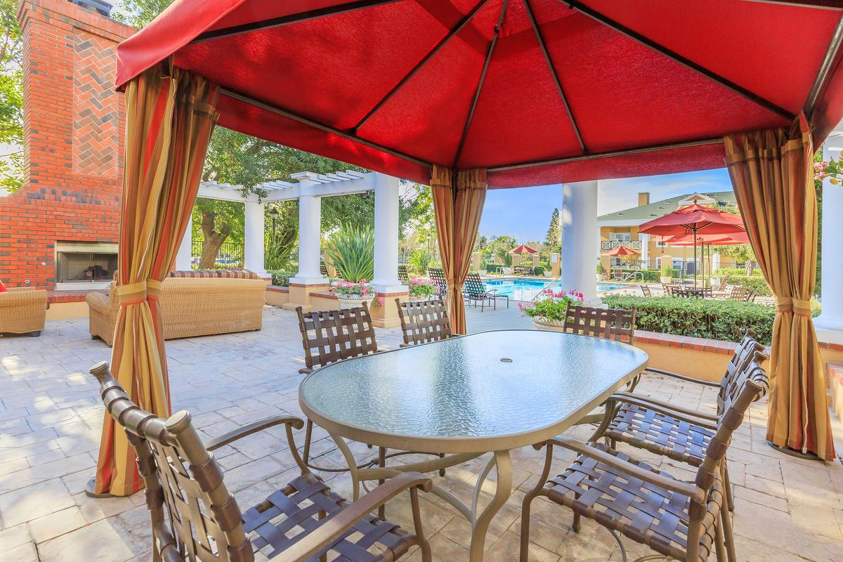 a dining room table with a red umbrella