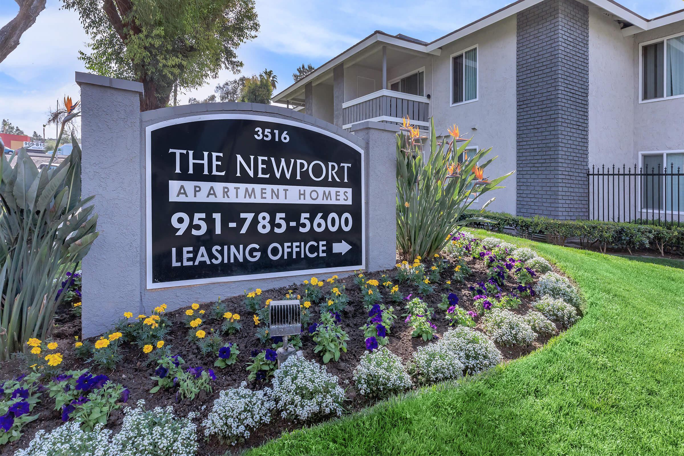 a sign above a flower garden