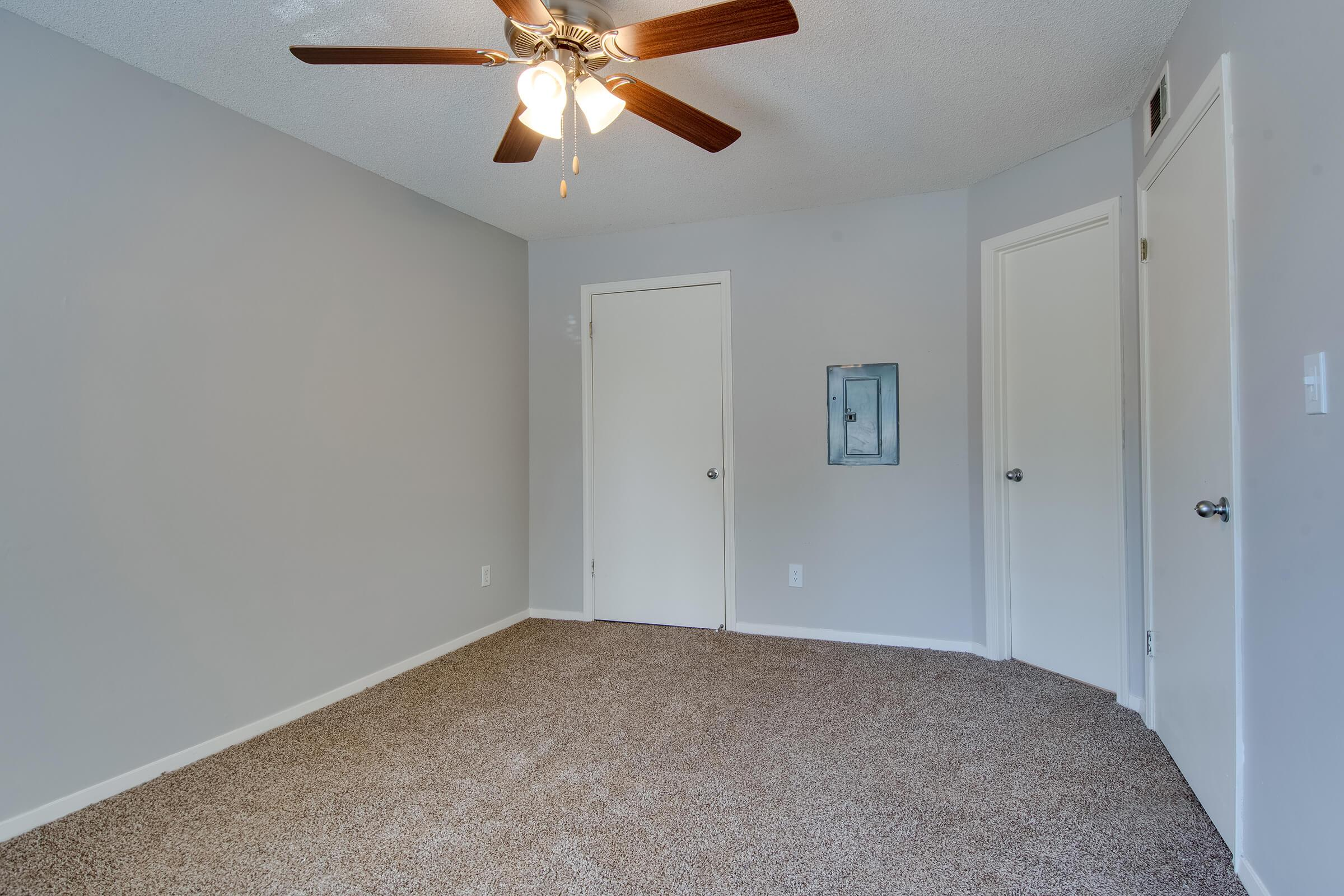 a bedroom with a ceiling fan