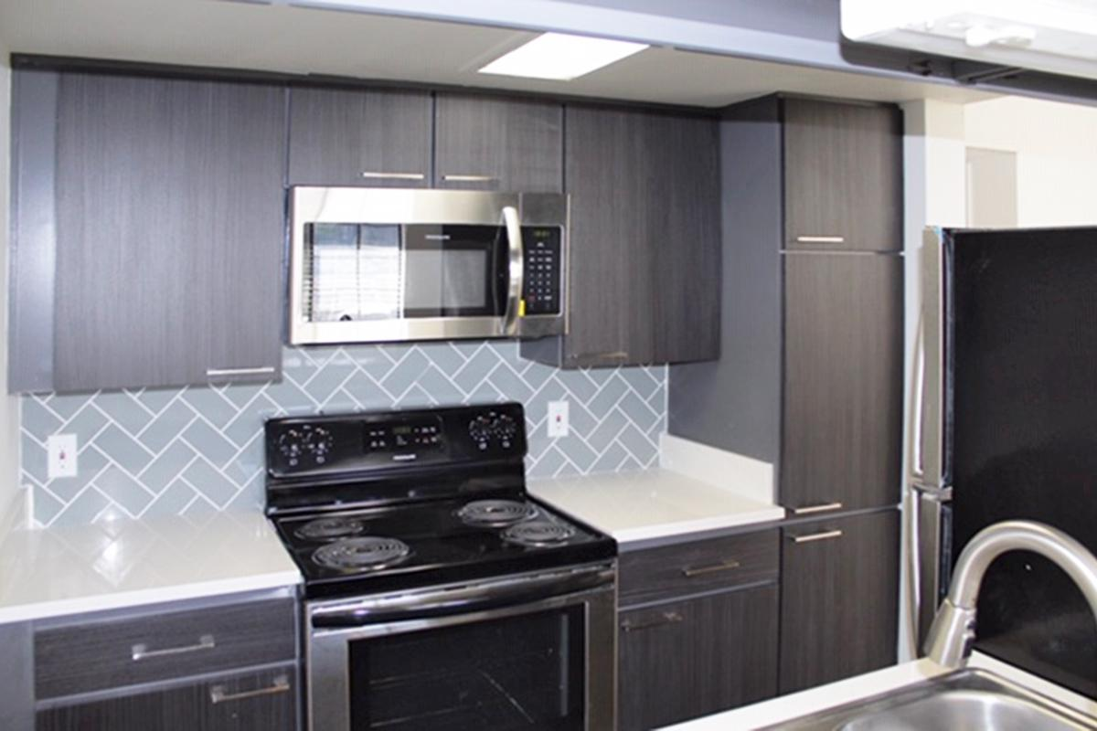 a black stove top oven sitting inside of a kitchen with stainless steel appliances
