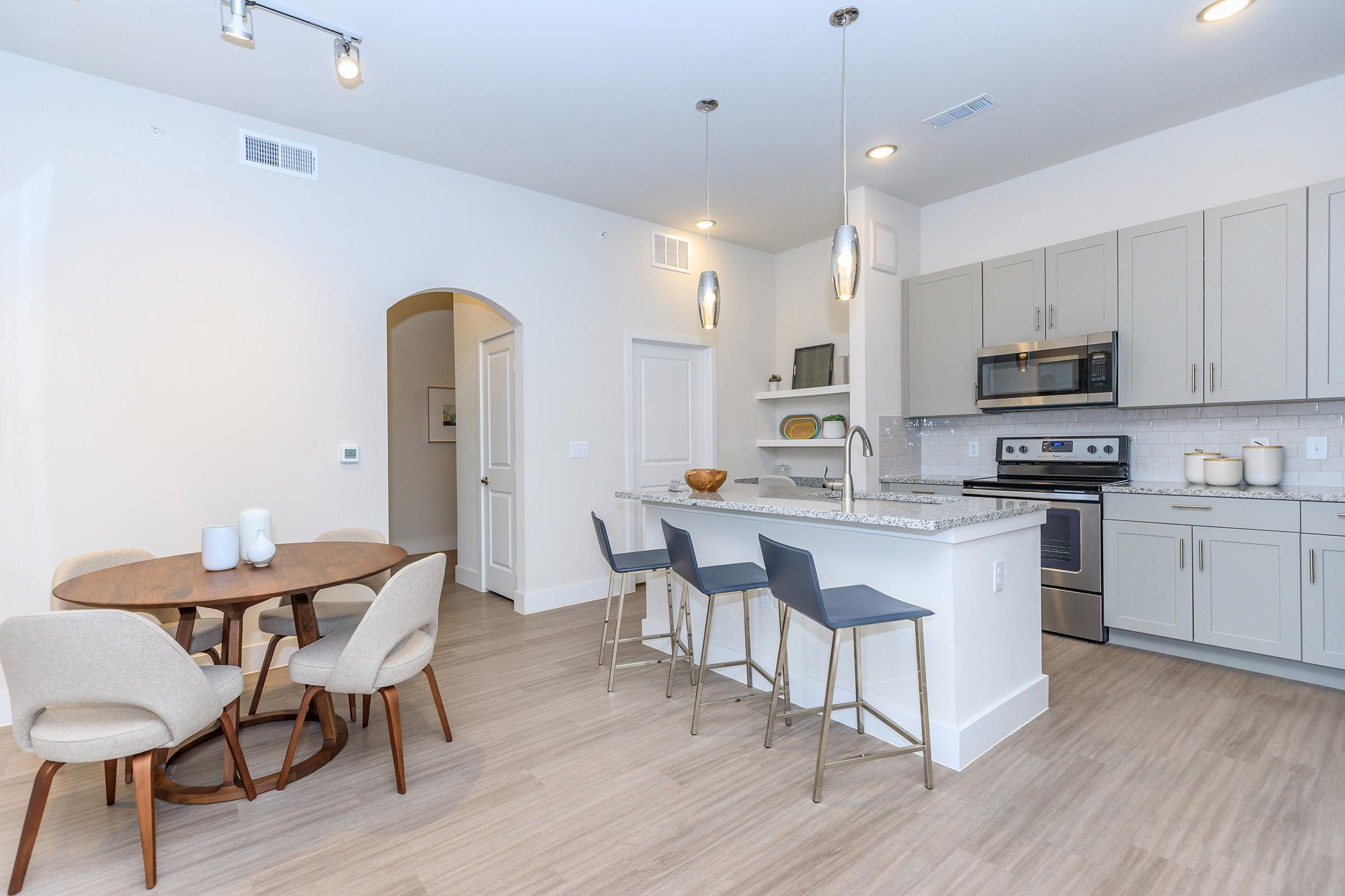 a kitchen with a table and chairs in a room