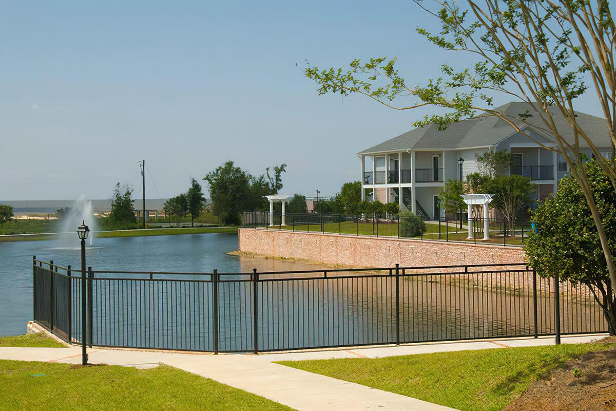 a house with a fence in front of a body of water