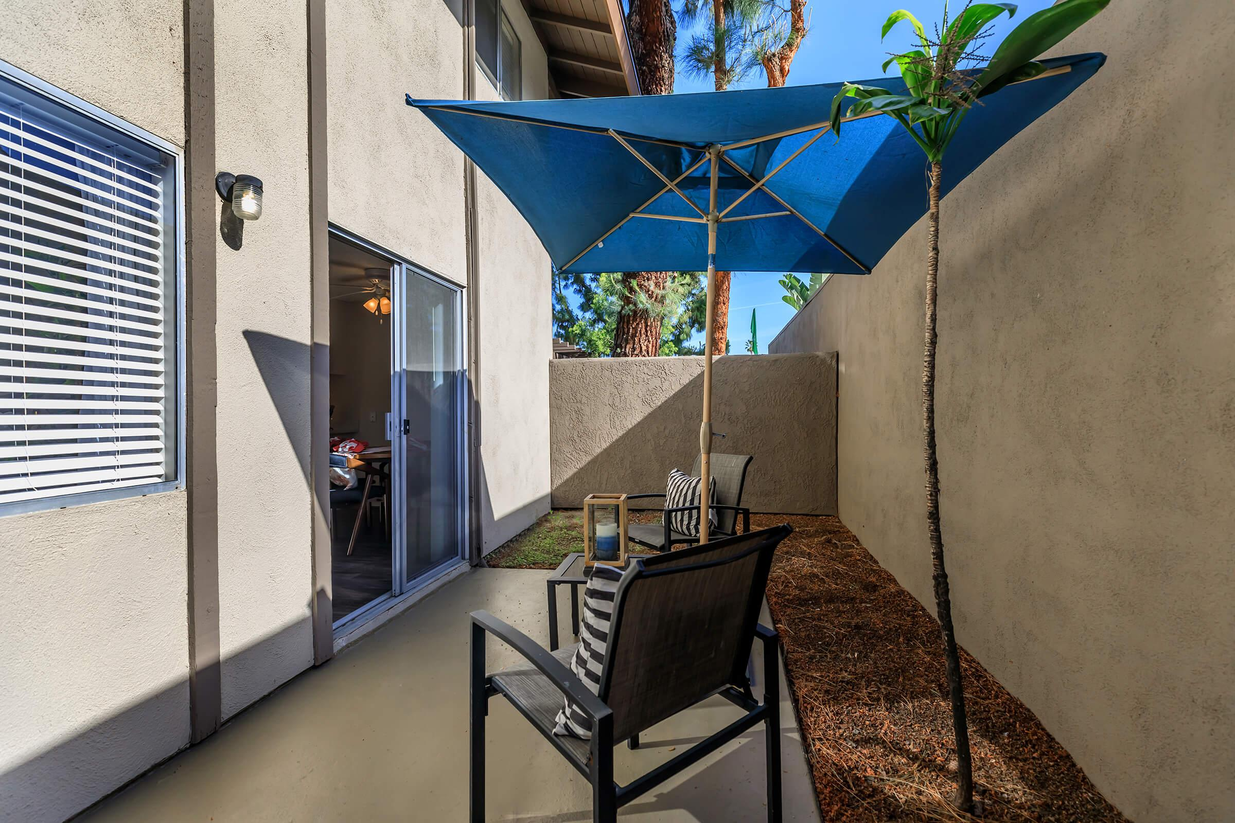 Patio with a table and blue umbrella
