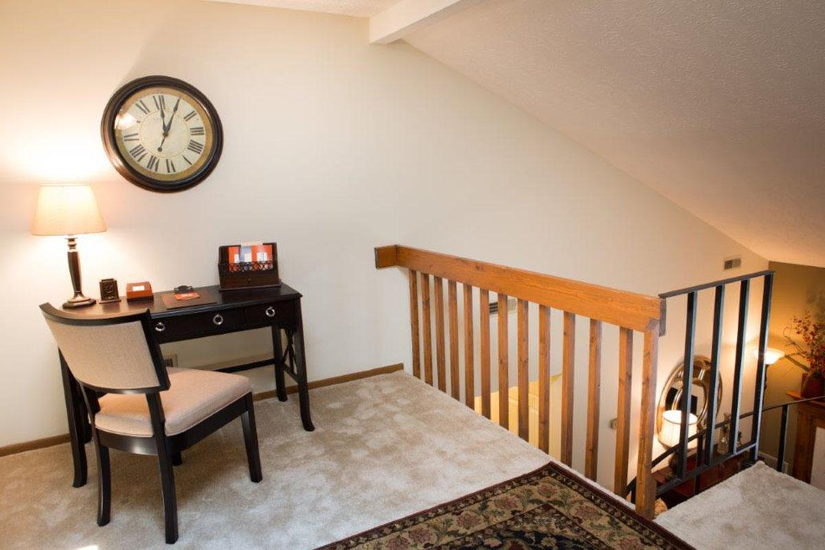 a living room with a clock at the top of a wooden table
