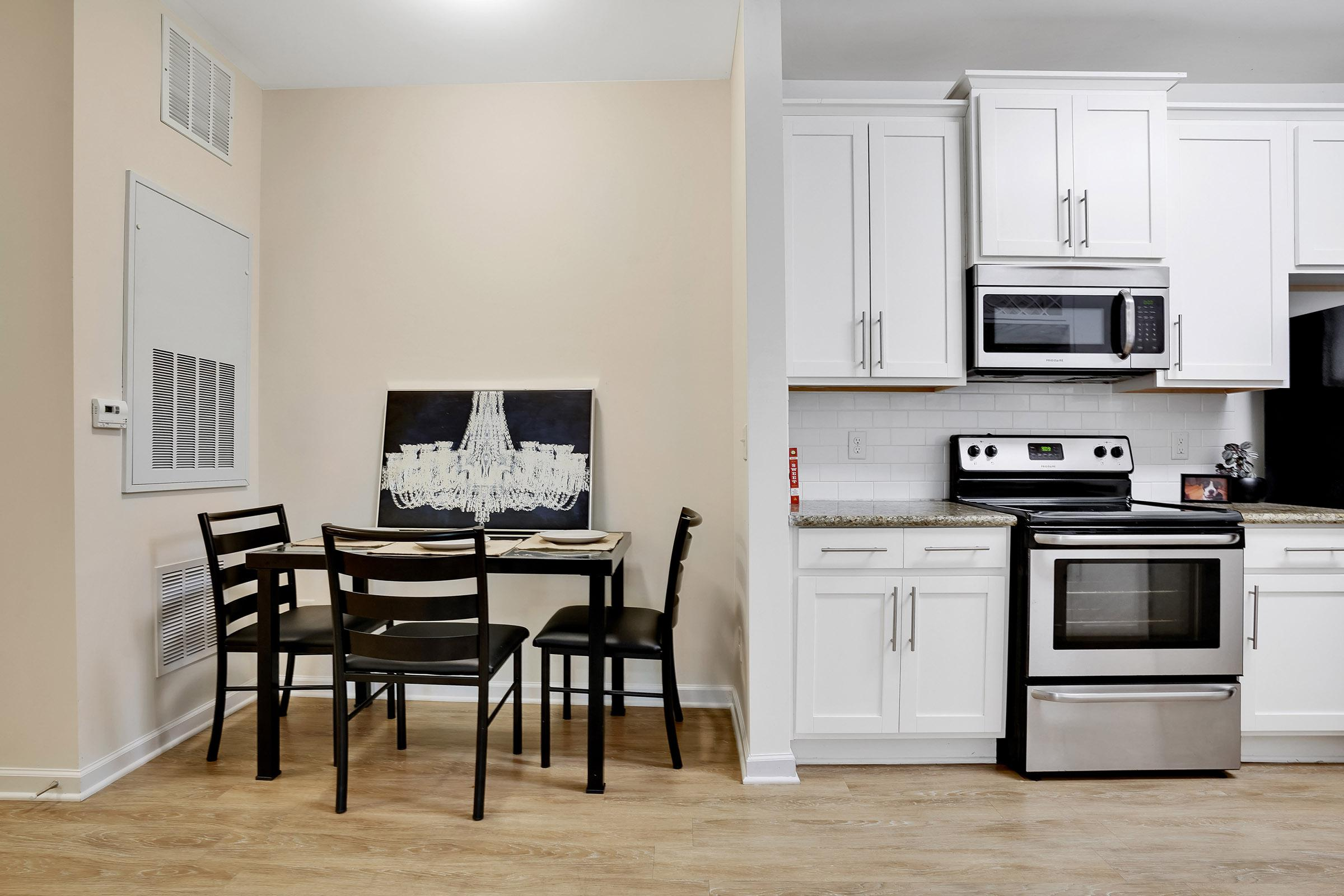 a kitchen with white cabinets and a black chair