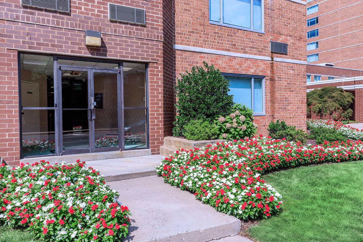 a colorful flower garden in front of a brick building
