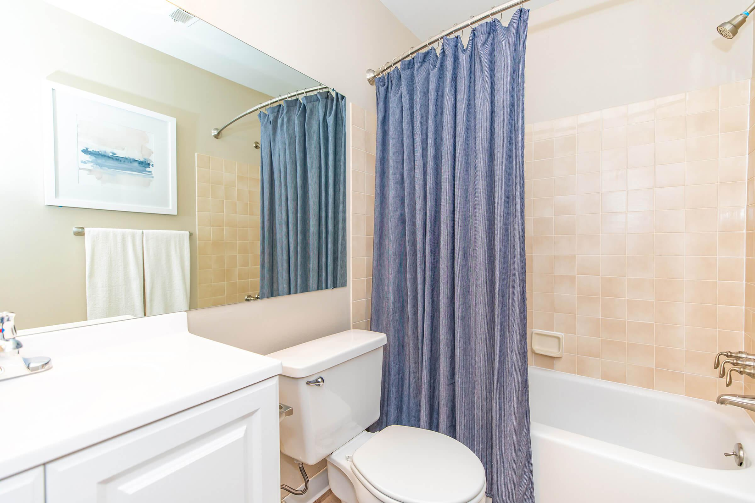 a room with a sink tub and shower curtain