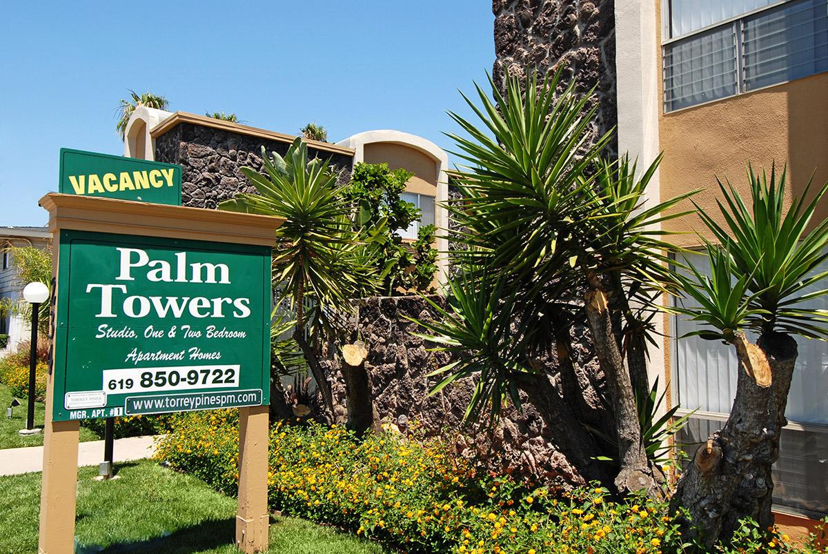 a sign in front of a palm tree
