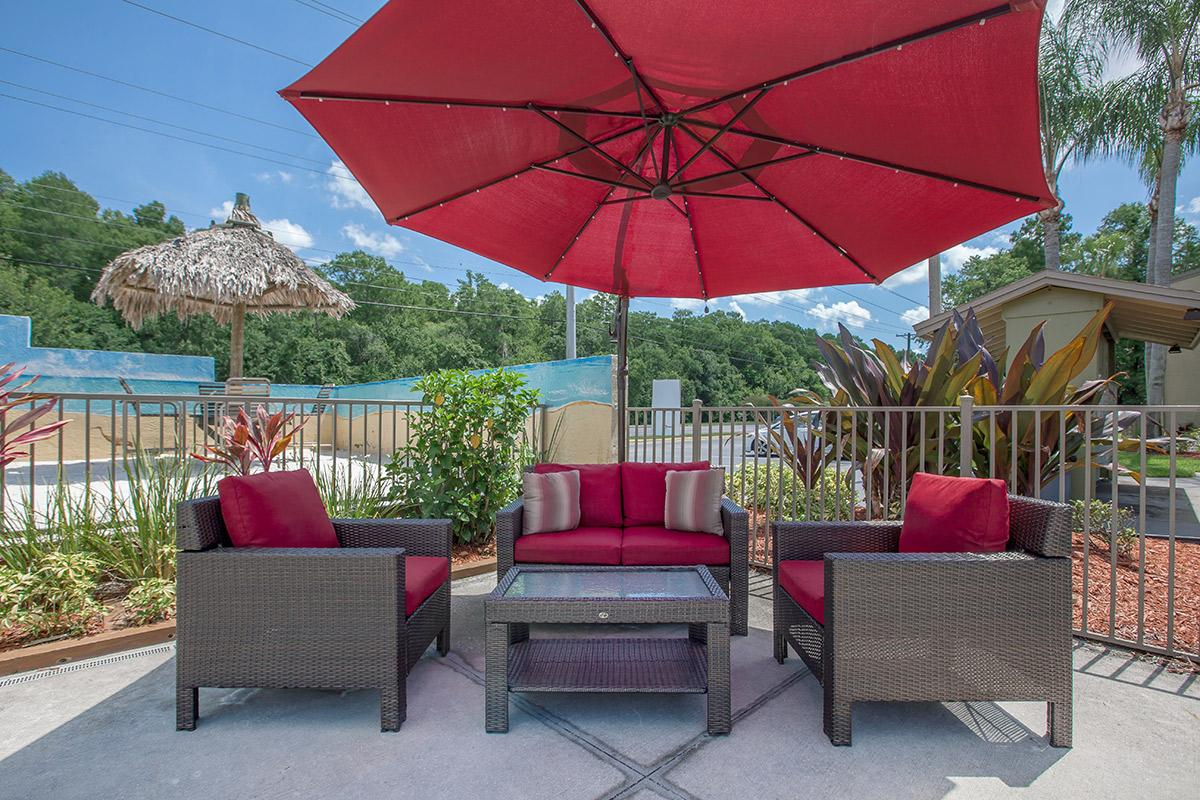 a large red chair in front of an open umbrella