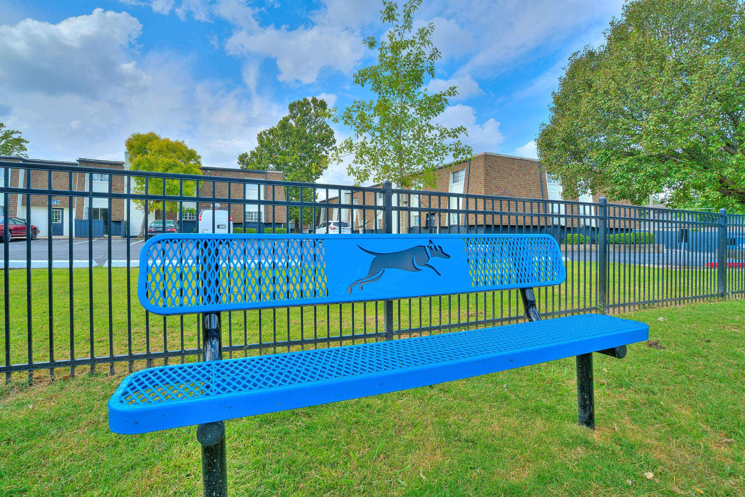 a blue bench in front of a fence