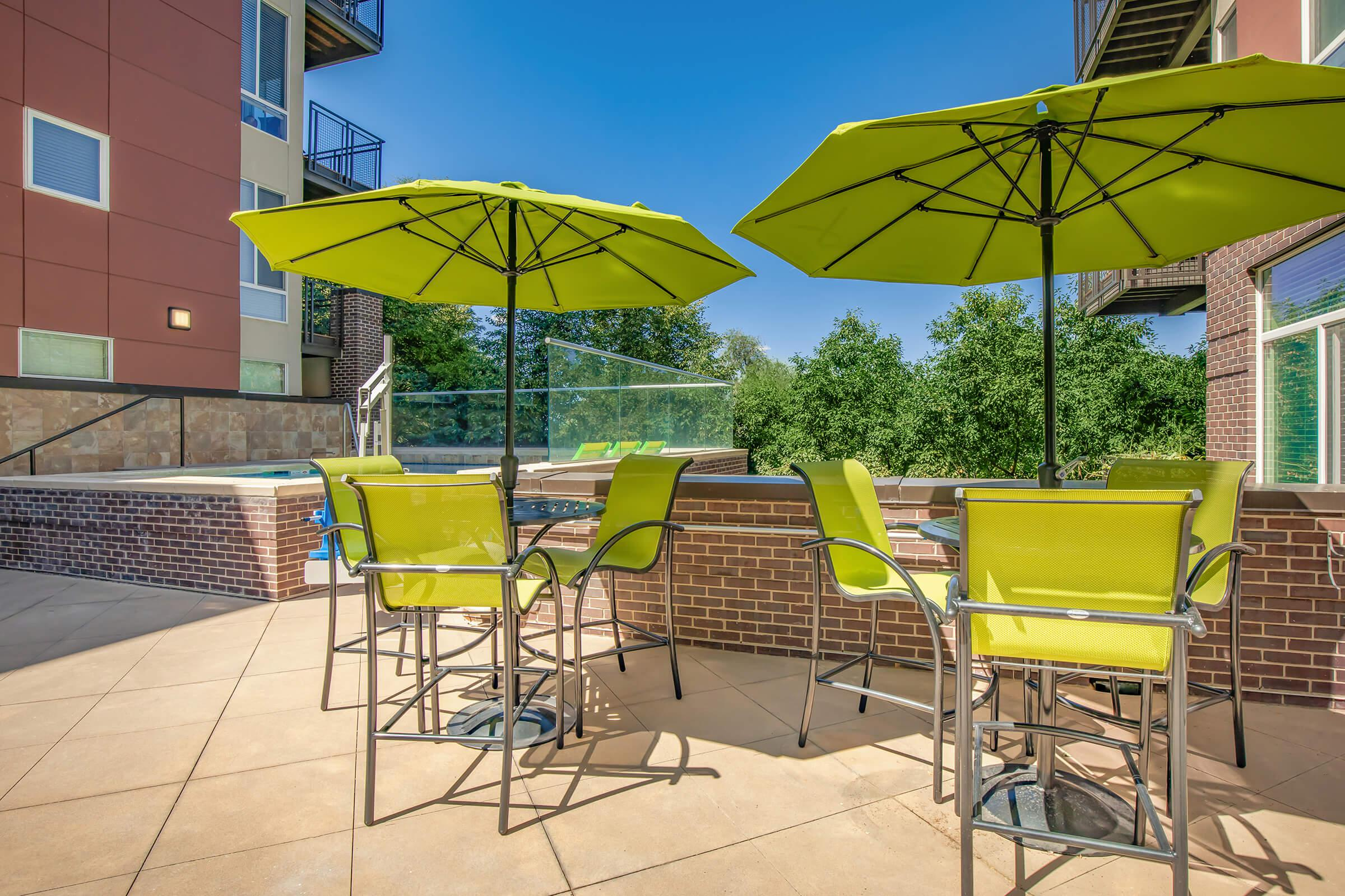 a group of lawn chairs sitting on top of a yellow umbrella
