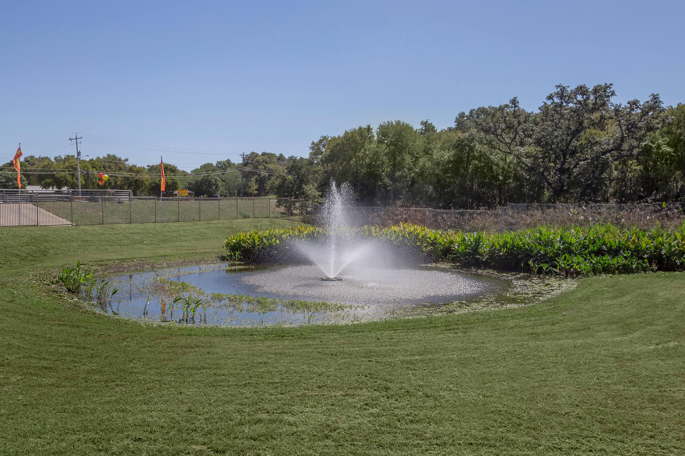 a close up of a water fountain in the middle of a field