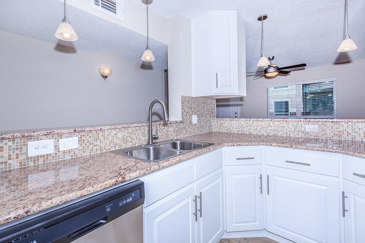 a kitchen with white cabinets and appliances