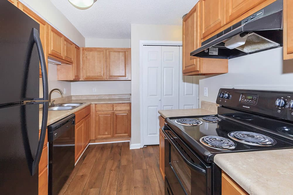 Modern black appliances compliment wood floors and cabinets in one of the kitchens at Van Mark Apartments in Monroe, LA