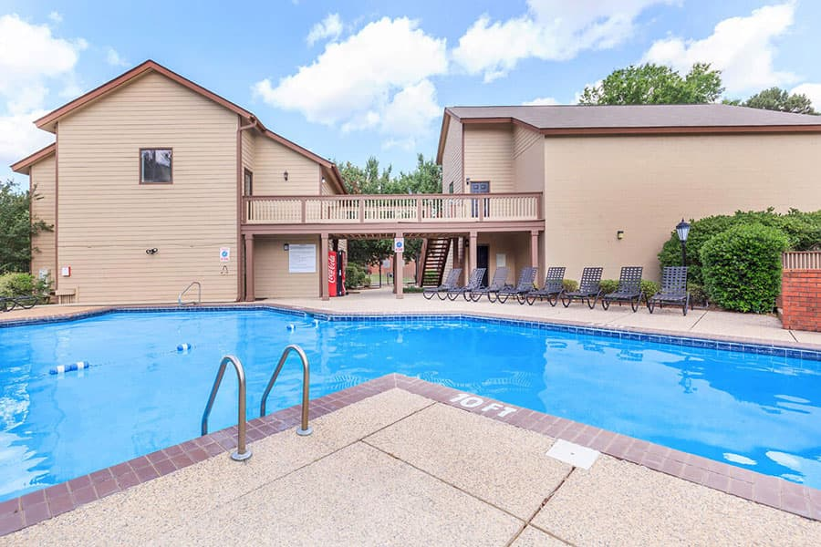The cool blue water of the swimming pool reflects the sky of a sunny day at Van Mark Apartments in Monroe, LA