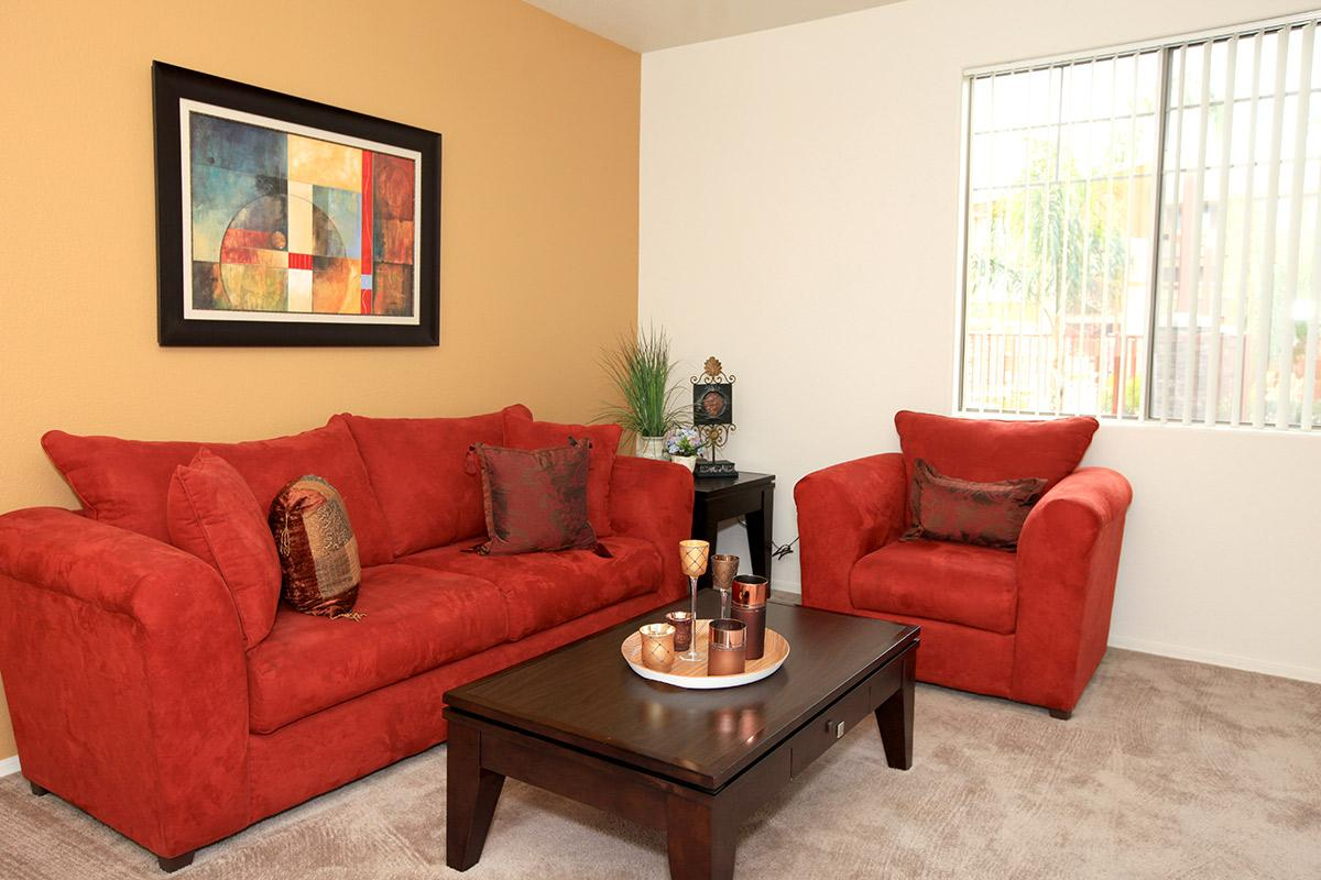 a red leather couch in a living room filled with furniture and a fireplace
