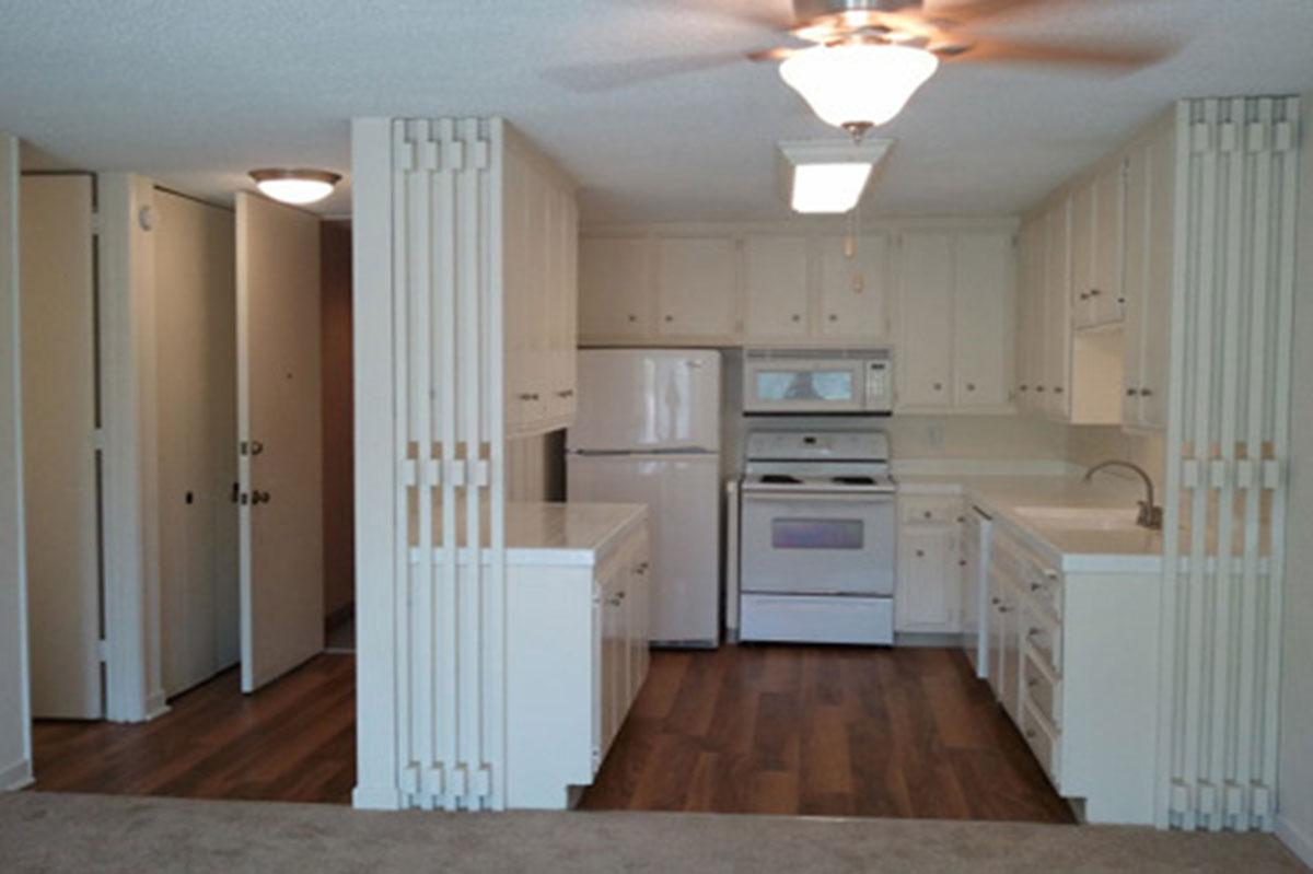 a kitchen with white cabinets and a wood floor