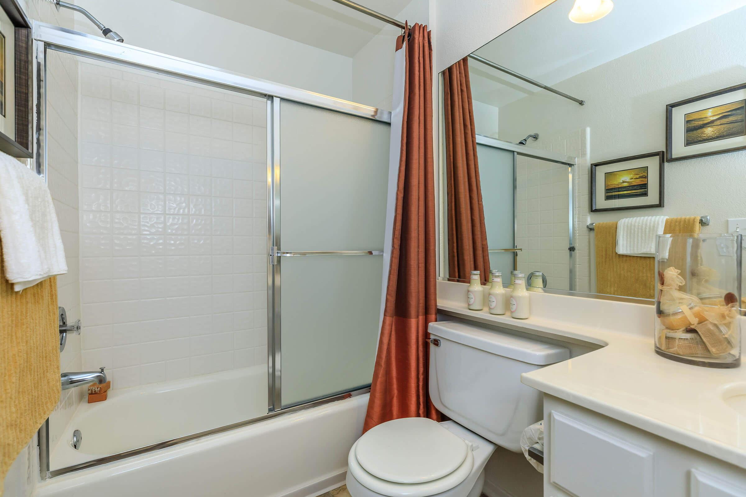 Bathroom with sliding glass shower door and red shower curtain