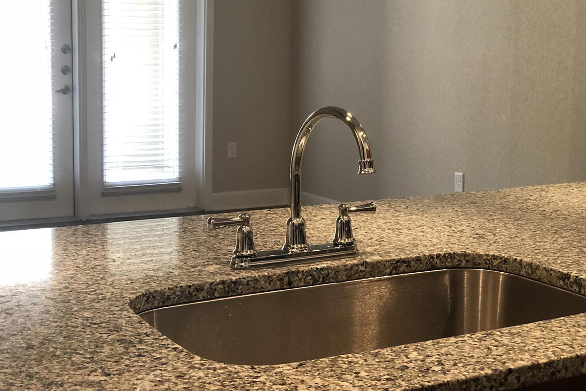 a counter with a sink and a window