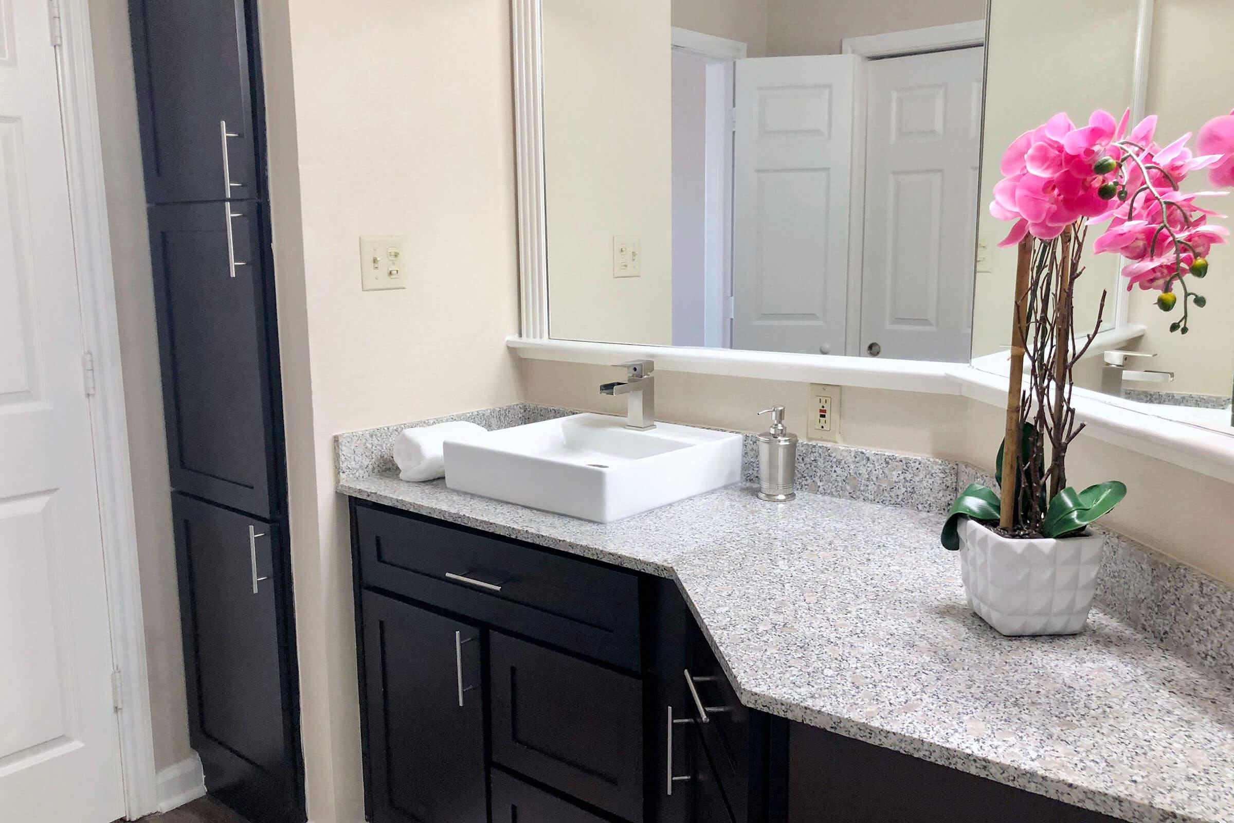 a vase of flowers next to a sink