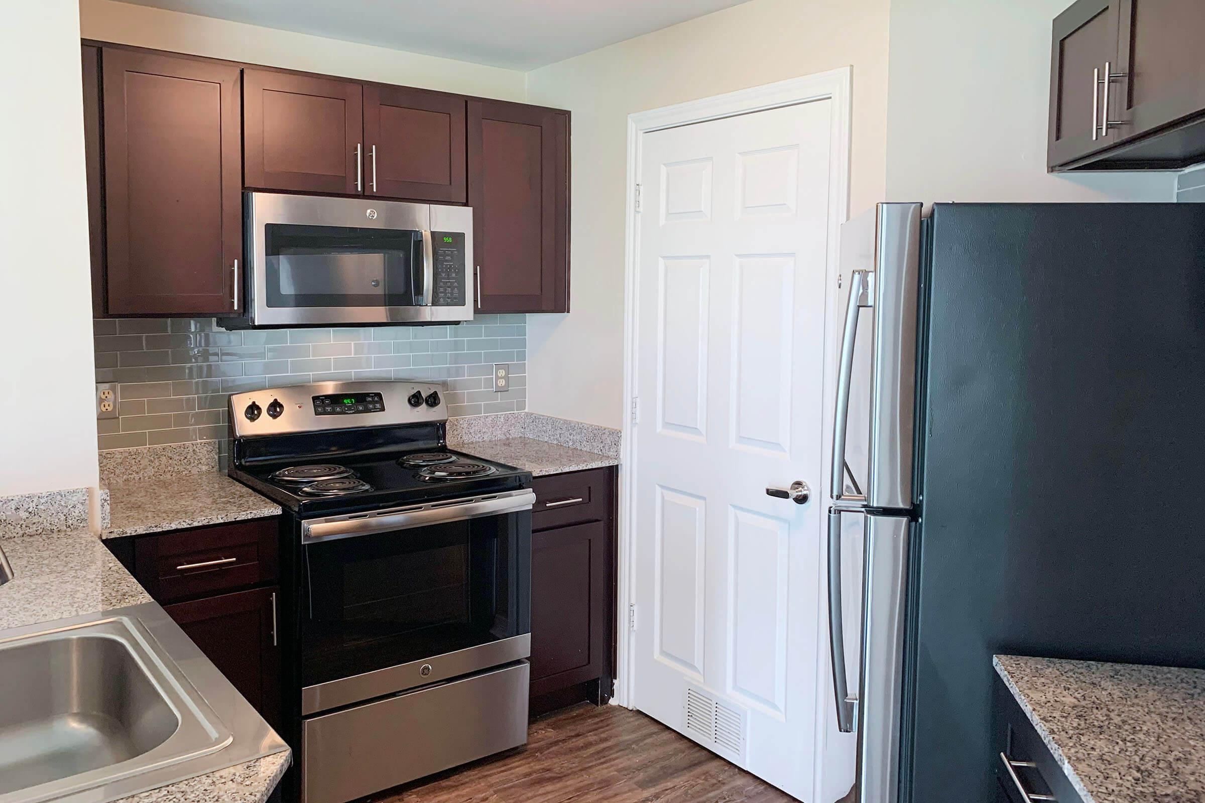 a kitchen with a stove a sink and a microwave oven on a counter