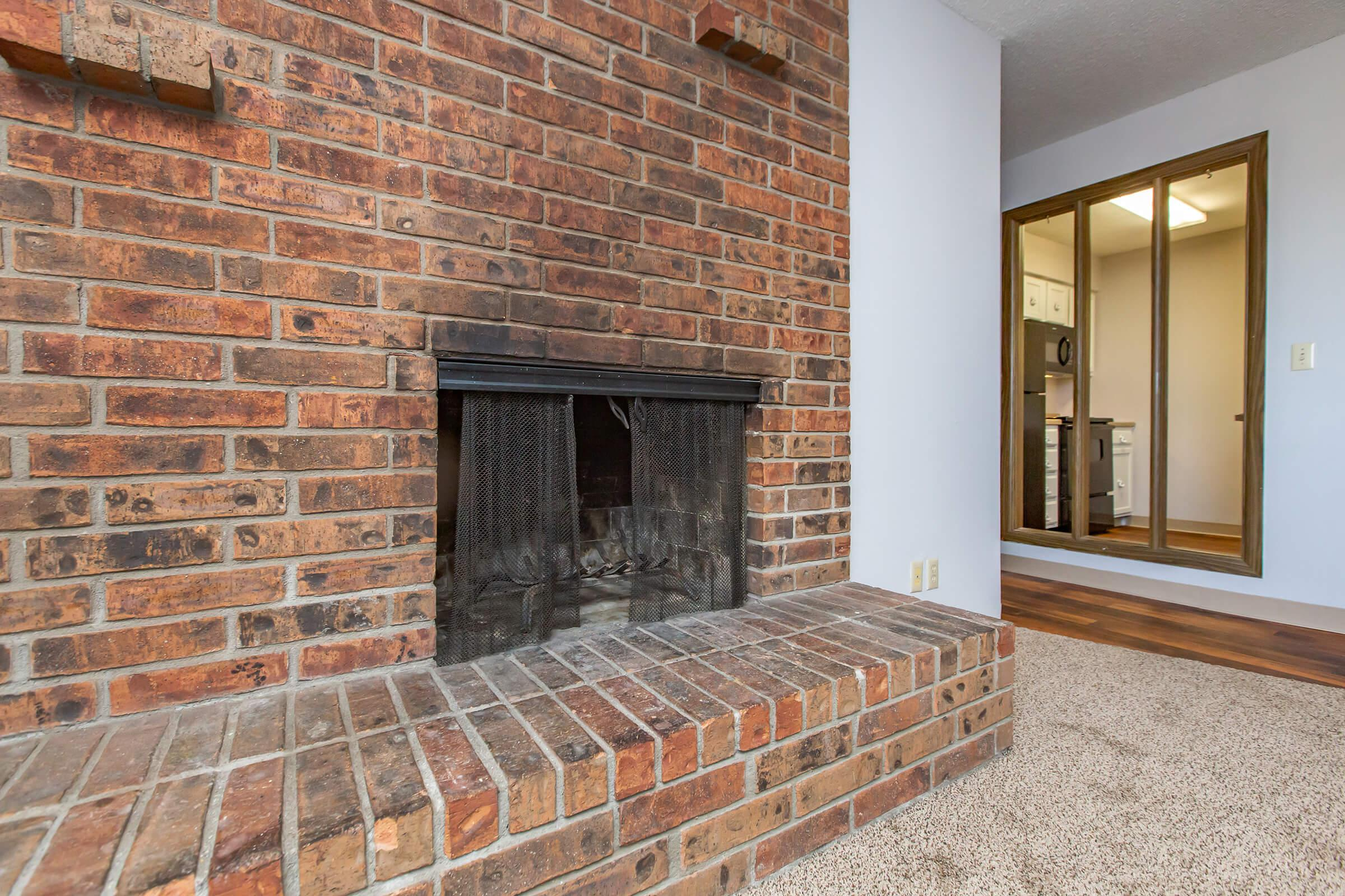 a room with a fireplace and a brick building