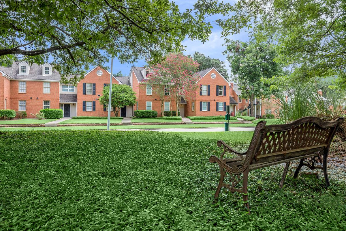 a couple of lawn chairs sitting on a bench in front of a house