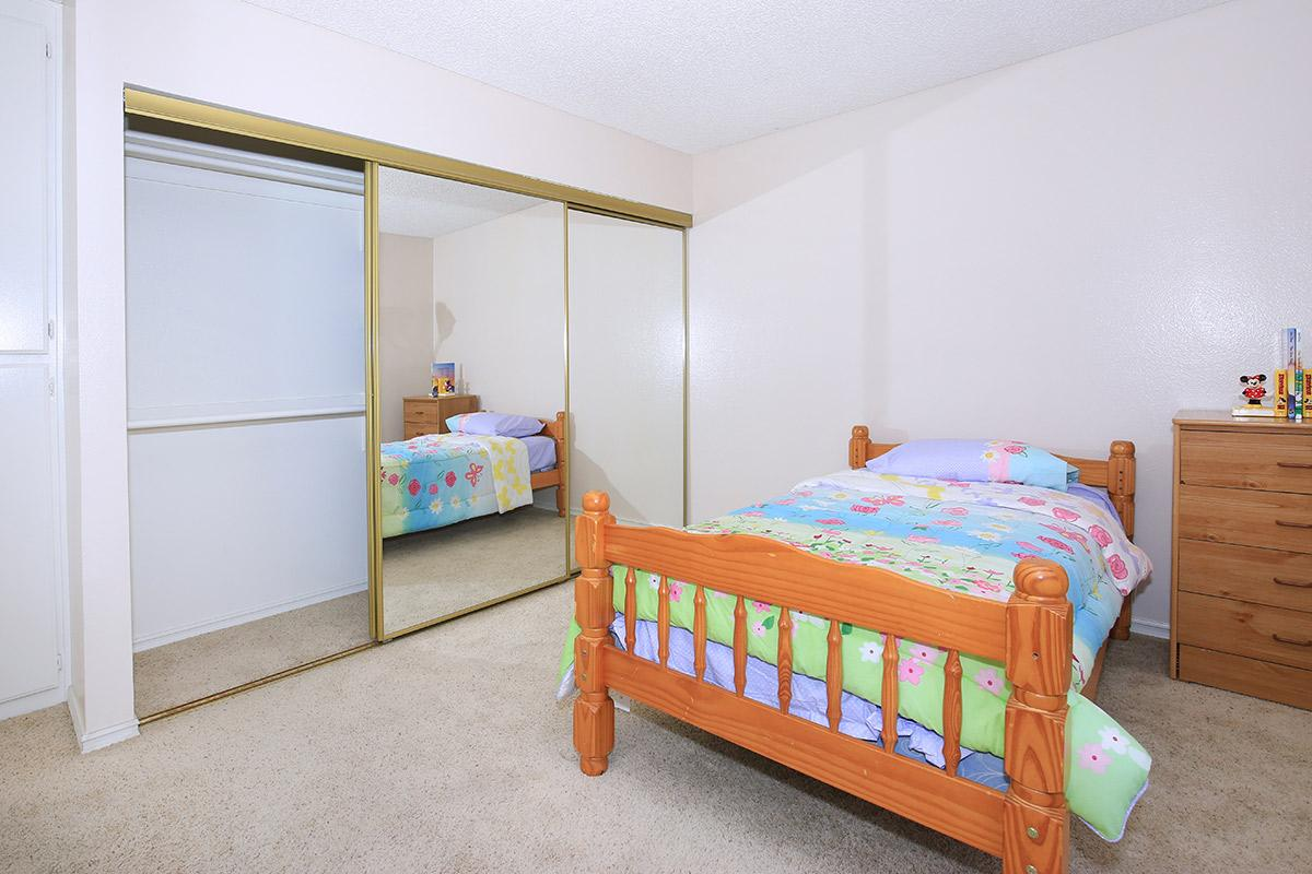 a bedroom with a bed and desk in a small room