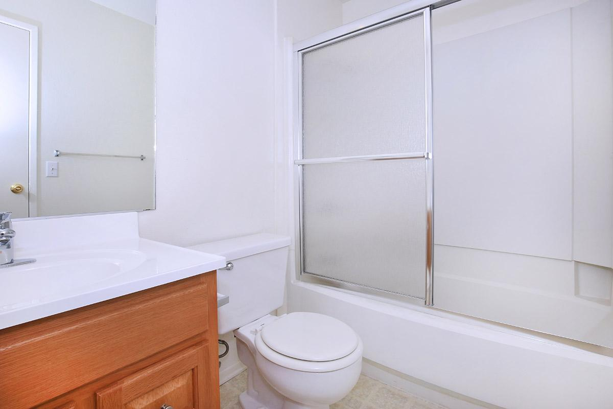 a white sink sitting next to a shower