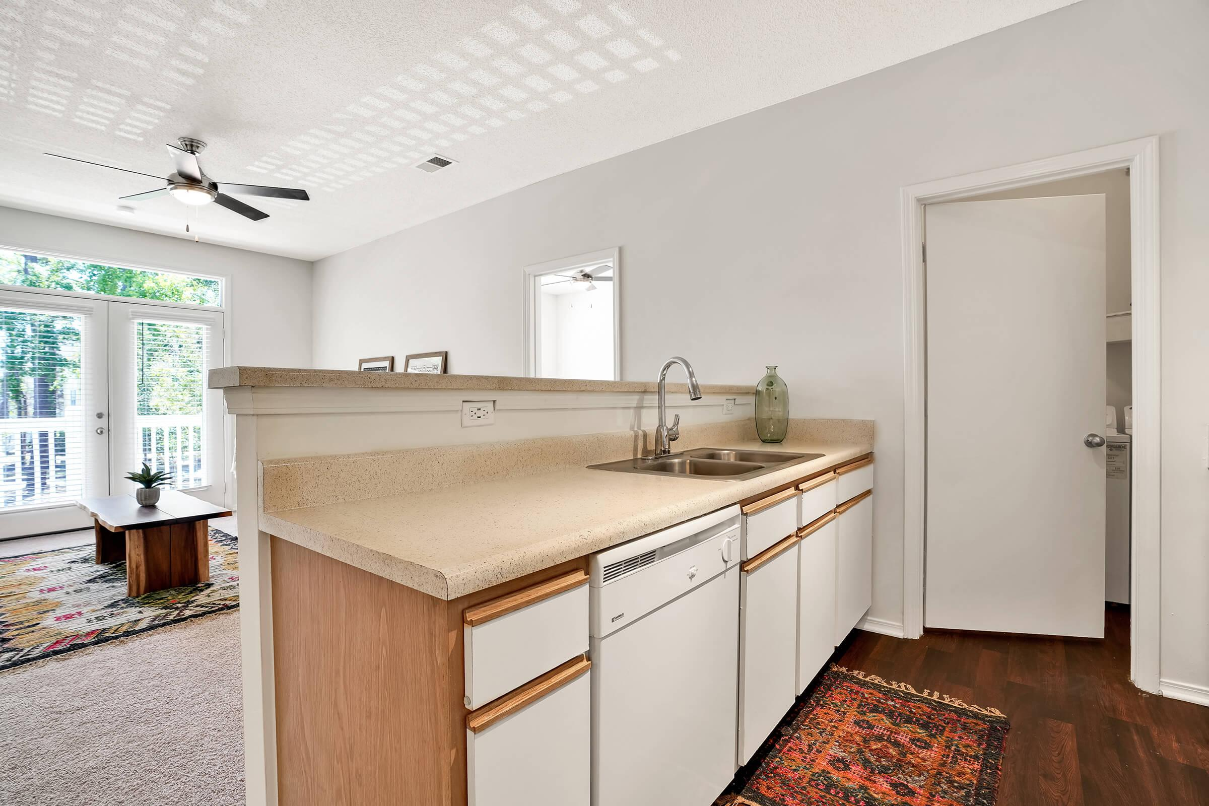 a kitchen with a sink and a mirror in a room
