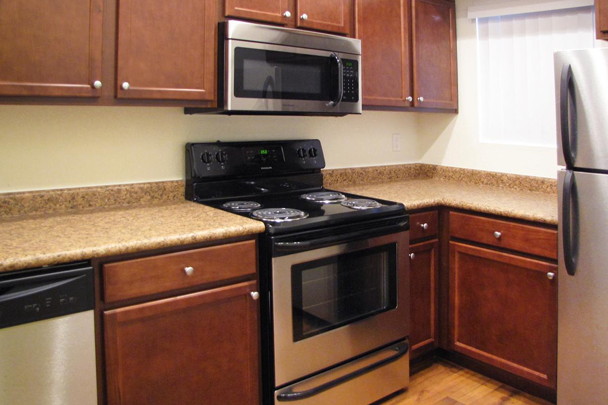 a kitchen with wooden cabinets and a black stove top oven