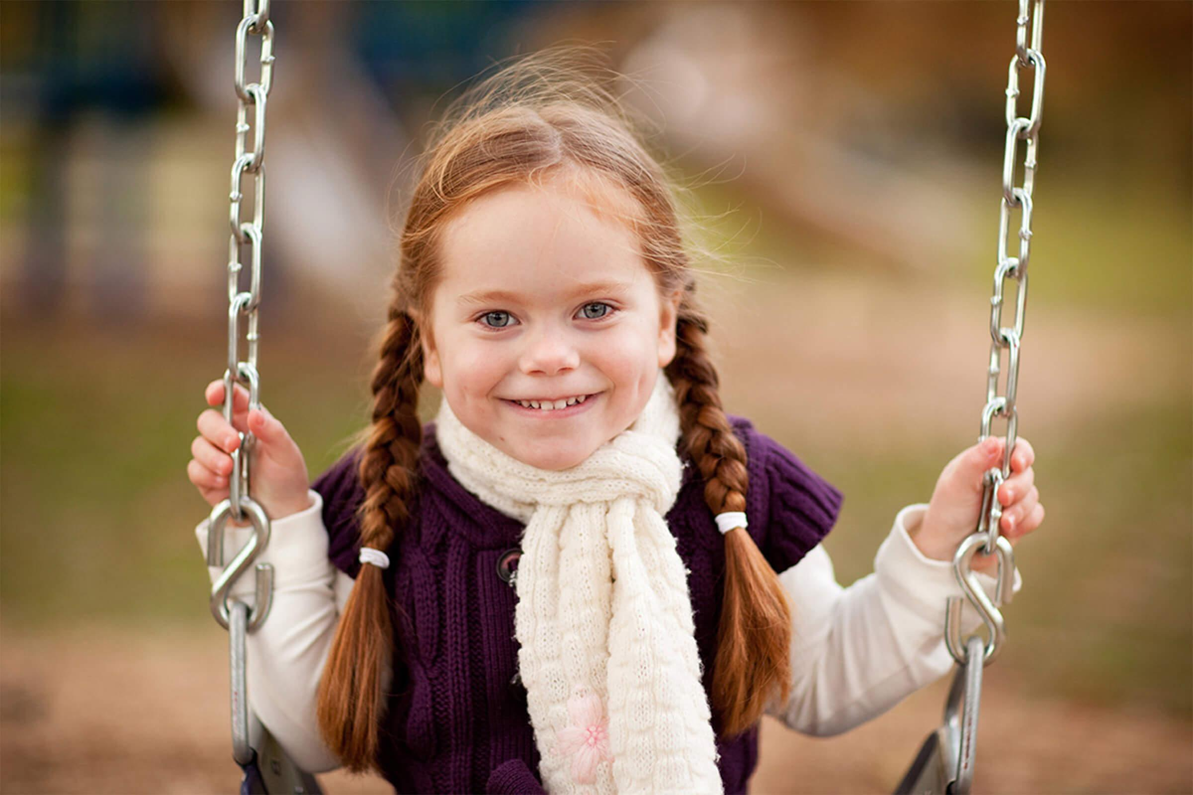 a girl is dressed in a swing