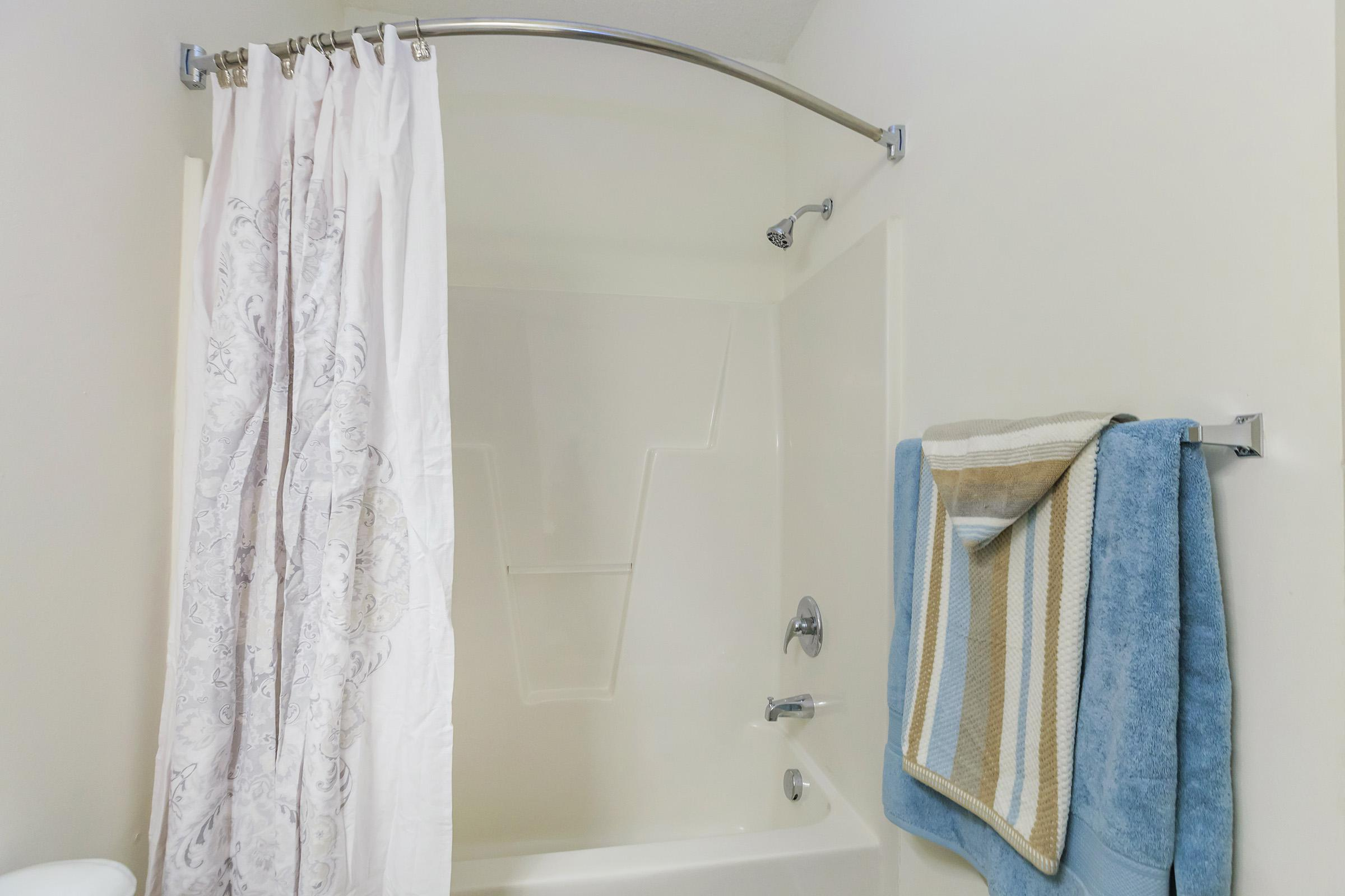 a white tub sitting next to a shower curtain