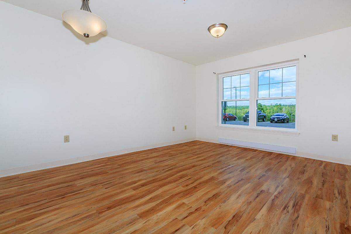 a bedroom with a wood floor